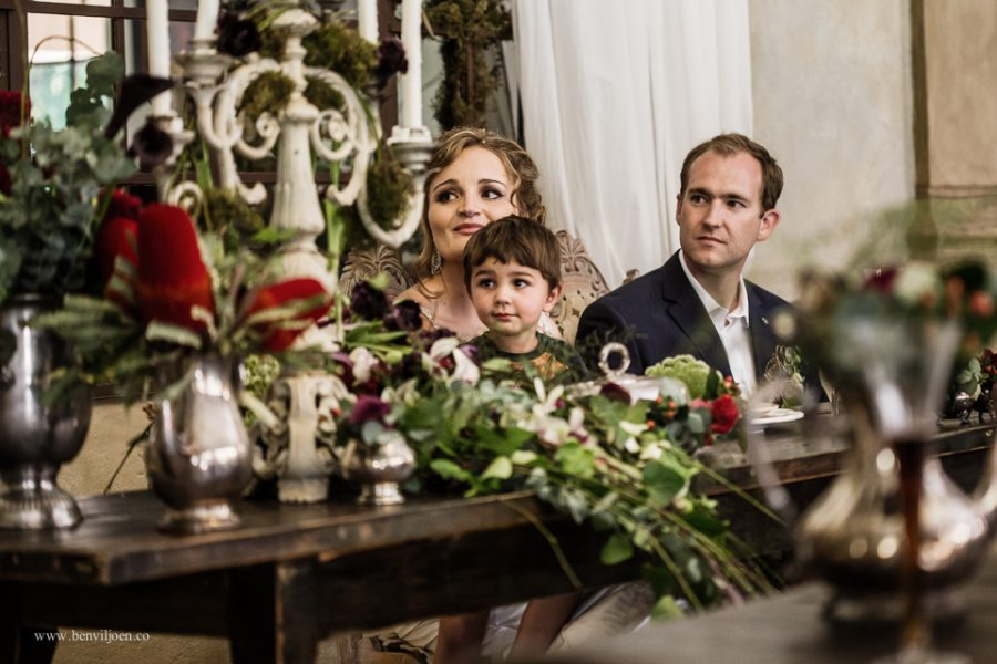 a child sits with a bride and listens to the reception speeches