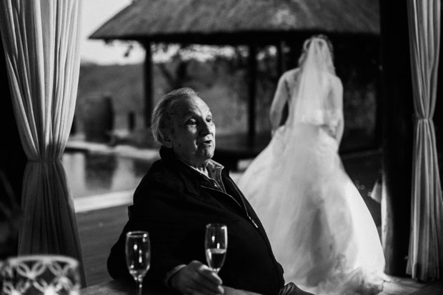 Grandfather at wedding with bride walking in the background
