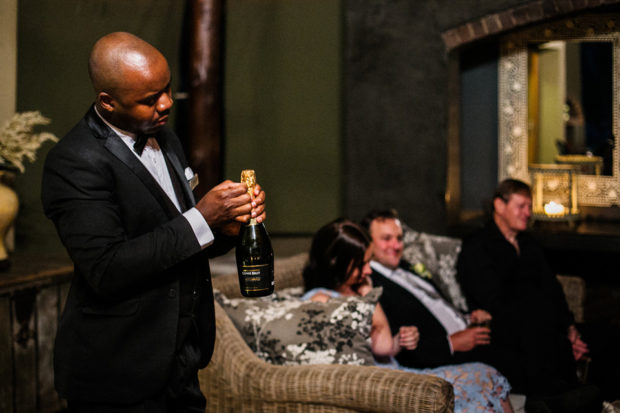 Waiter opening champagne at laid back wedding in Africa