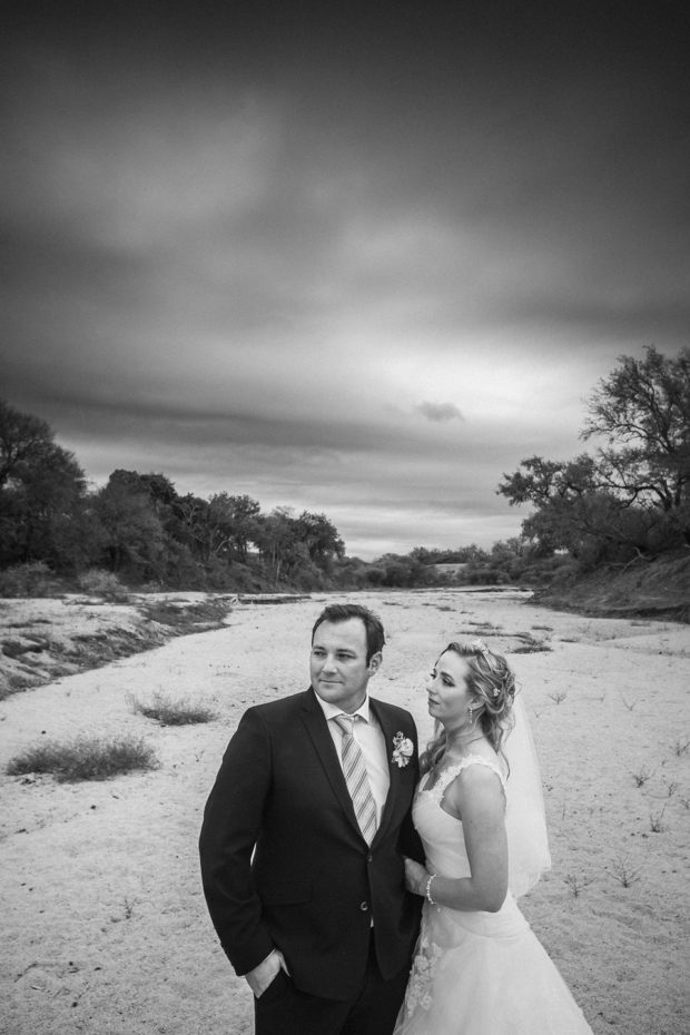 dramatic portrait of bride and groom in a dry riverbed in the bushveld