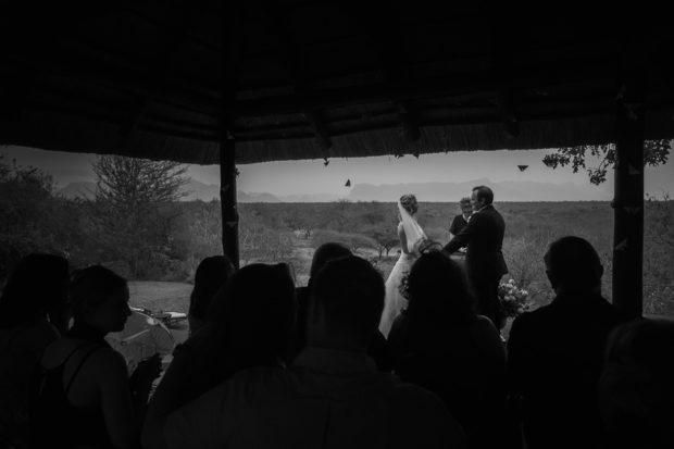 View of wedding ceremony from the back with mountains in background