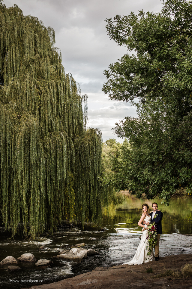 Bride & groom on the banks of the serene early autumn Vaal river in Parys