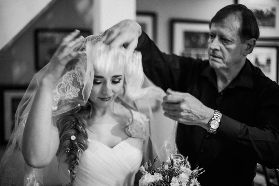 Father lifting bridal veil